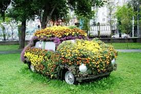 Car covered in flowers and plants.